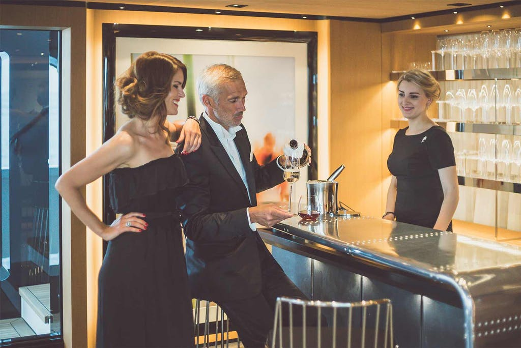 Couple getting a drink at the bar aboard SUERTE
