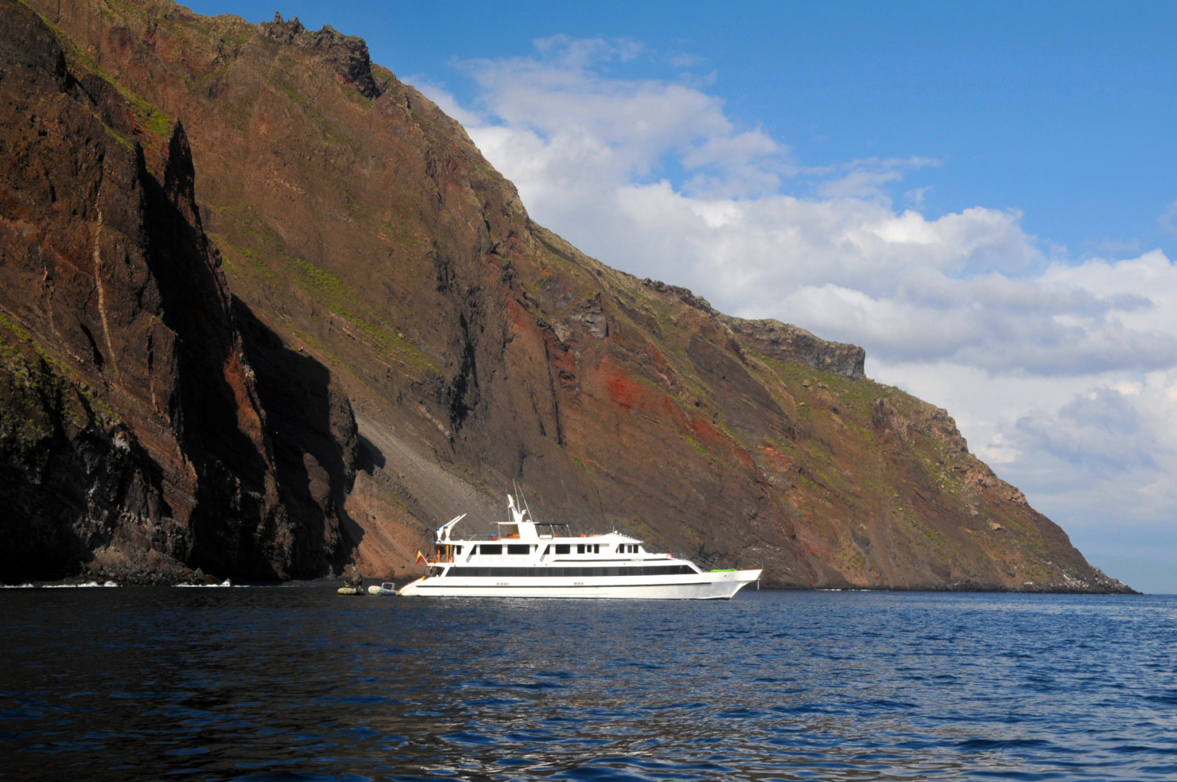 Integrity luxury yacht charter in Galapagos off rocky coast