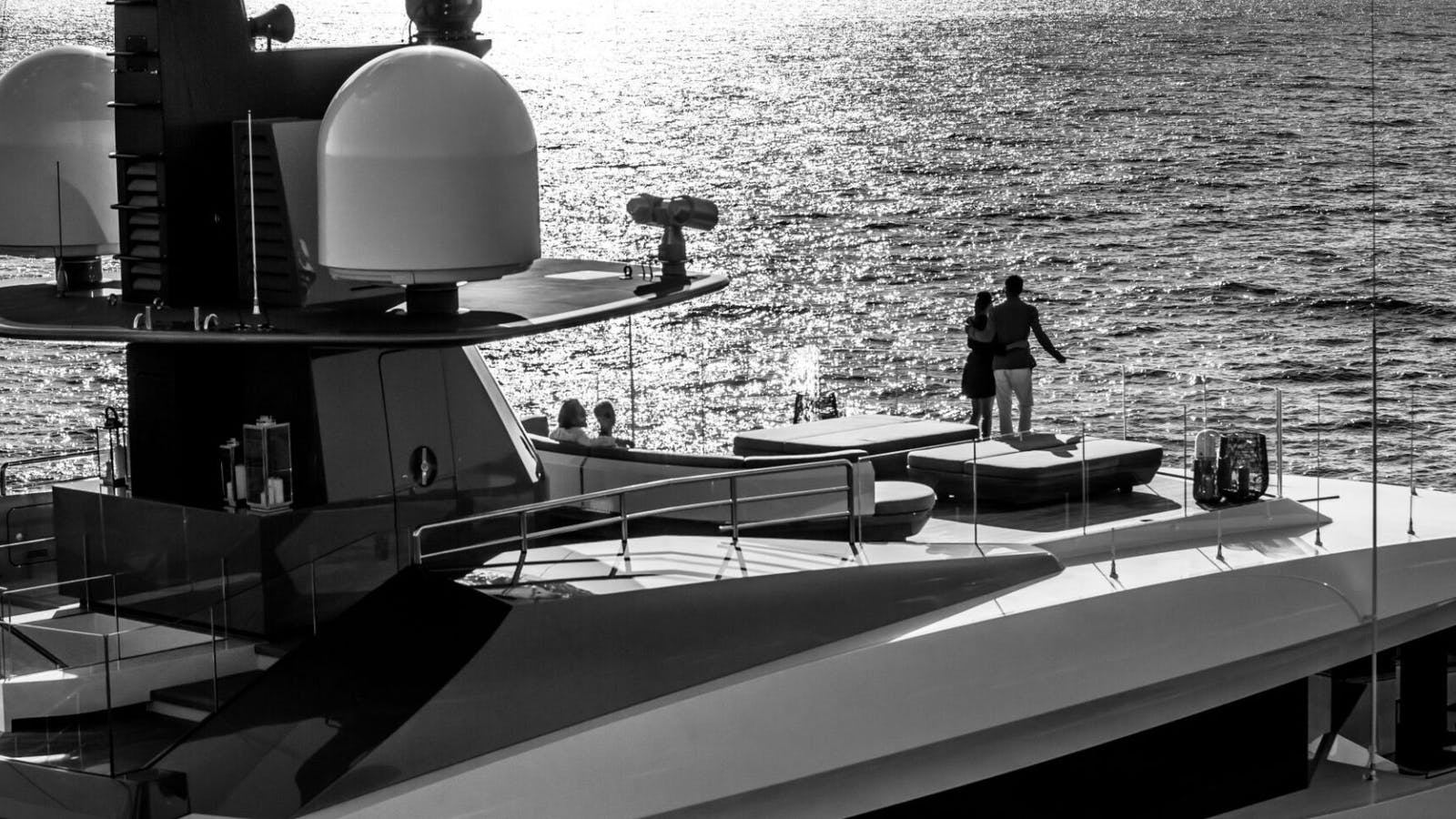 Couple looking into horizon onboard sun deck of a superyacht for sale