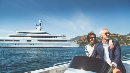 older couple cruising on yacht tender with superyacht in backgroundd