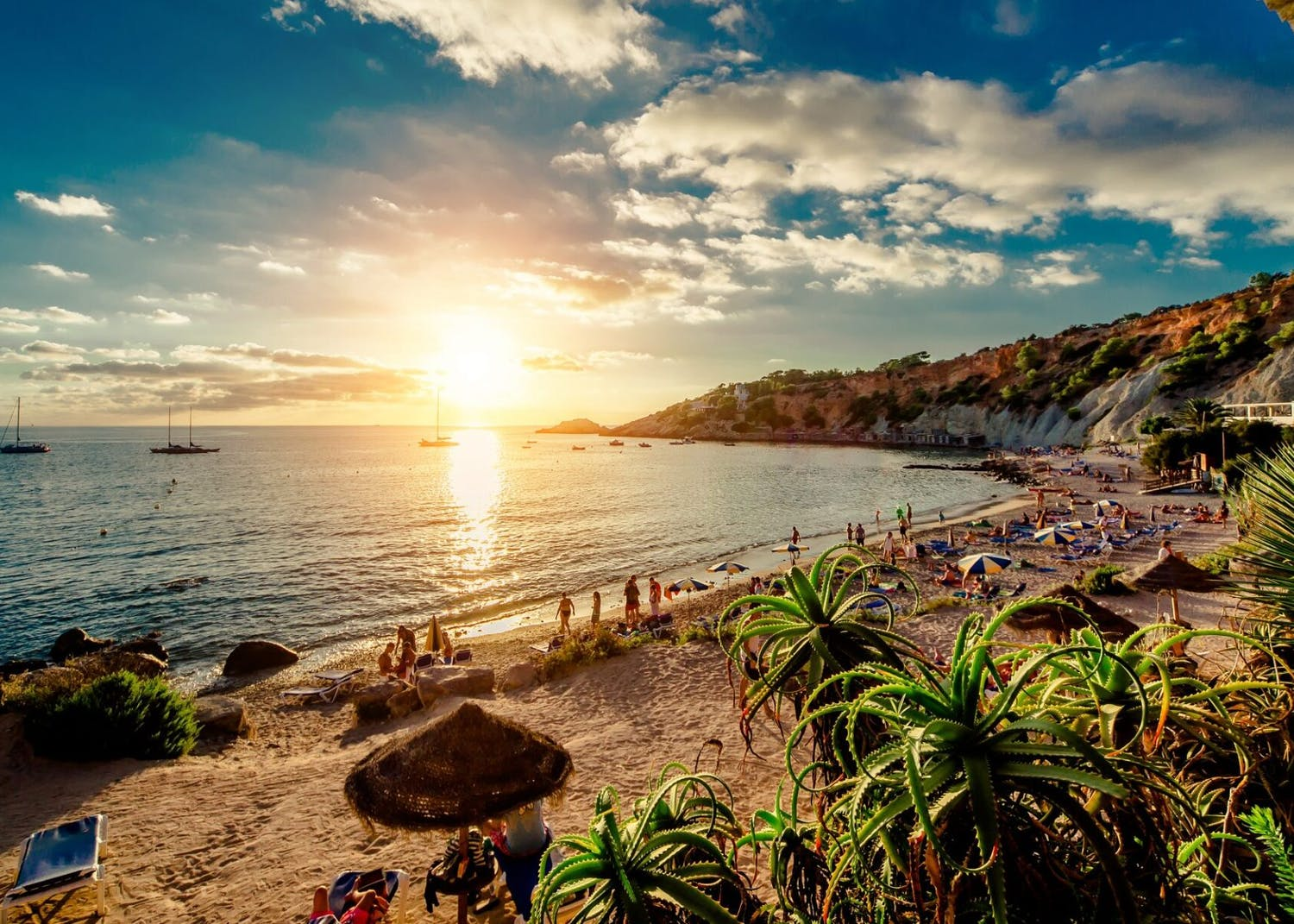 Sunset over luxury beach villas and Balearics superyachts for charter in Ibiza Spain