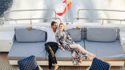 Couple relaxing onboard superyacht while underway