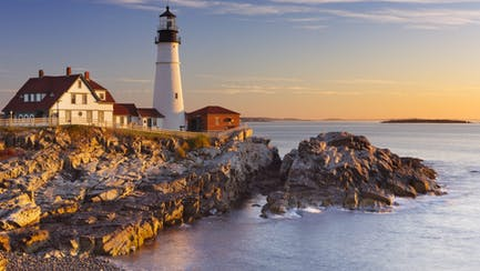 Sunrise view of lighthouse during sunrise from a yacht charter in New England