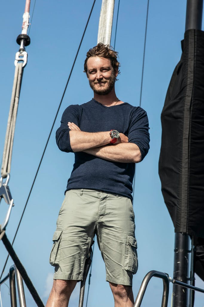 A man standing on the deck of a sailing yacht with a Richard Mille watch