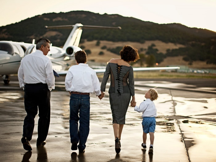 Family walking to a private jet