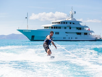 Wakeboarding in front of a yacht