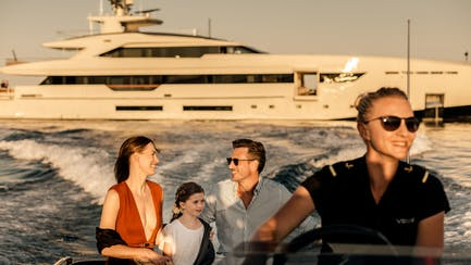 Mediterranean superyacht charter guests aboard a tender in front of Mega Yacht