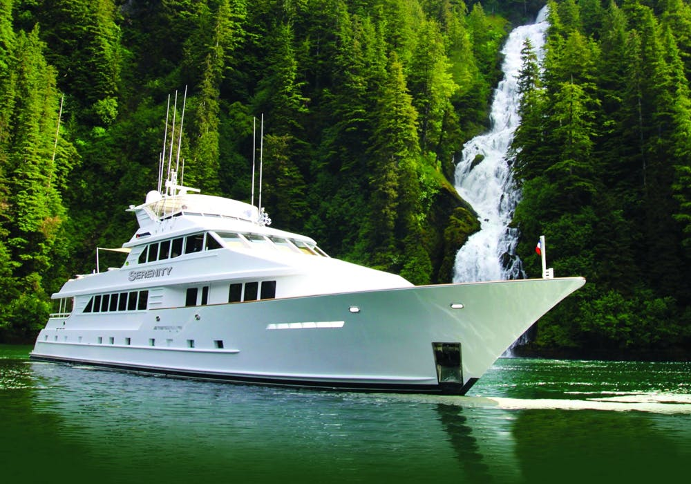 Charter Yacht Serenity in front of a waterfall in Alaska