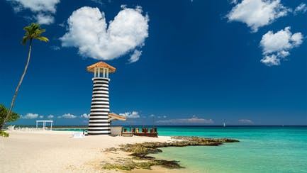 idyllic private beach and luxury yacht in Dominican Republic with heart shaped cloud and turquoise waters