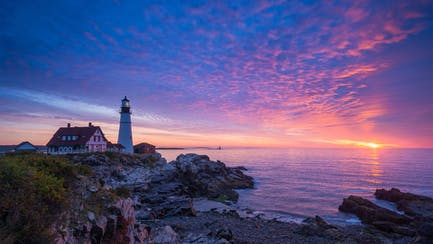 private luxury yacht charter on the north american coast with lighthouse at sunrise