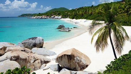 BVI superyacht charter near Virgin Gorda private boulder beach with white sand and palm trees