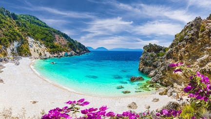 white sand beach with clear blue Caribbean ocean and luxury yacht charters in the virgin islands