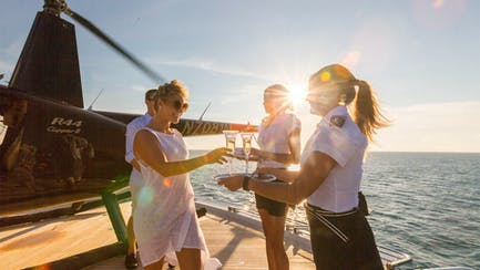 luxury yacht charter crew serving drinks to charter guests on helipad in Caribbean sea