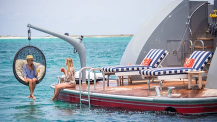 luxury yacht charter with women couple relaxing on yacht beach club in the Caribbean ocean