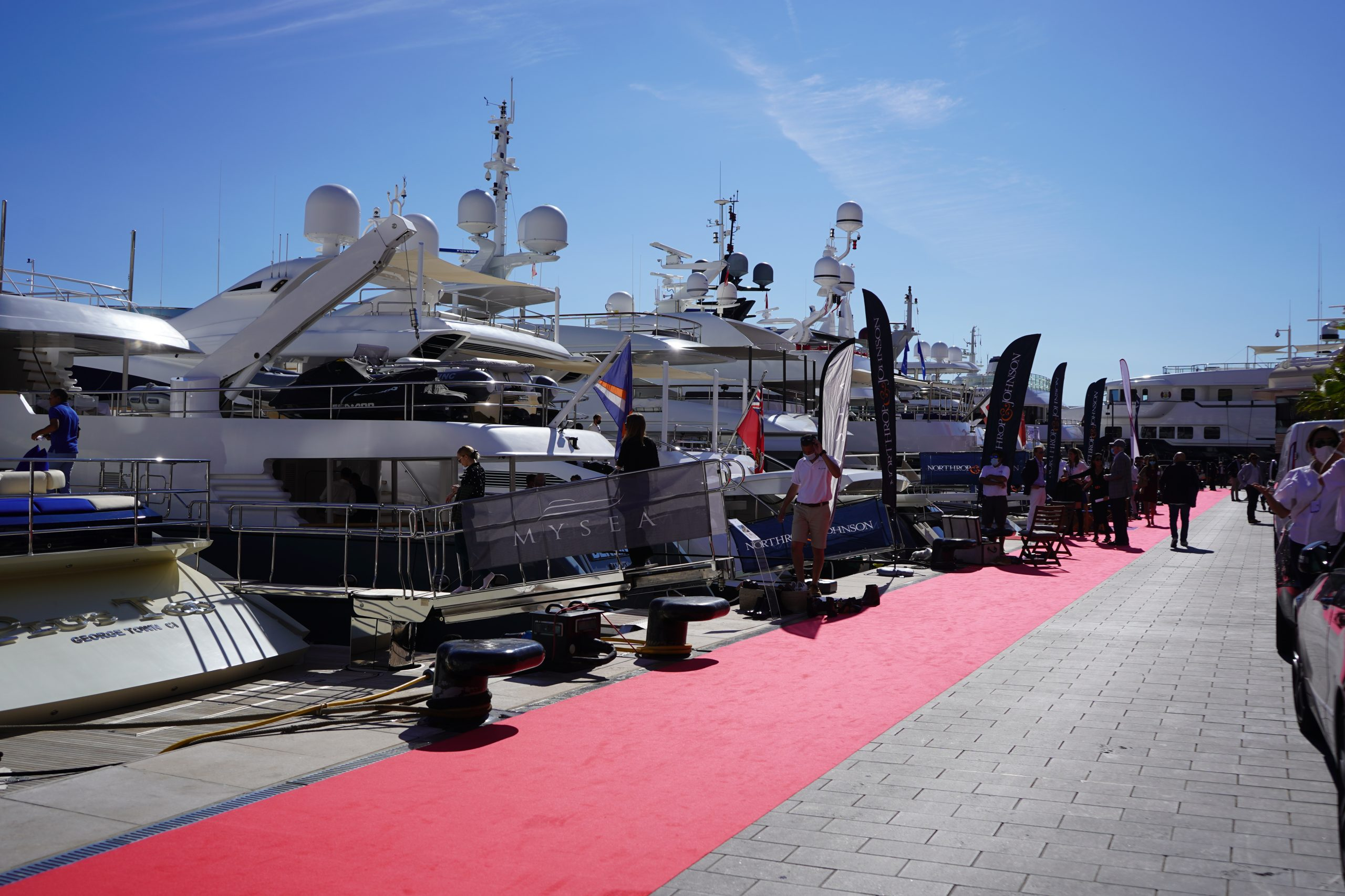 Cluster Yachting Monaco - Open Day Dock with red carpet, Northrop & Johnson flags and yachts
