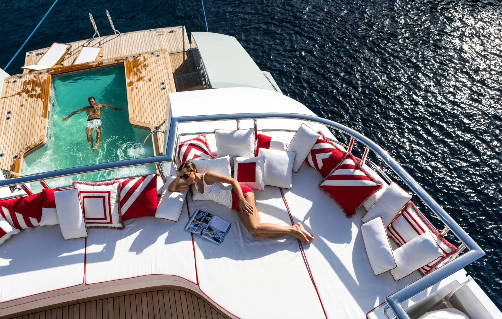 236-foot (72m) AXIOMA charter yacht sundeck with a girl reading and a guy in the pool on the main deck aft swimming