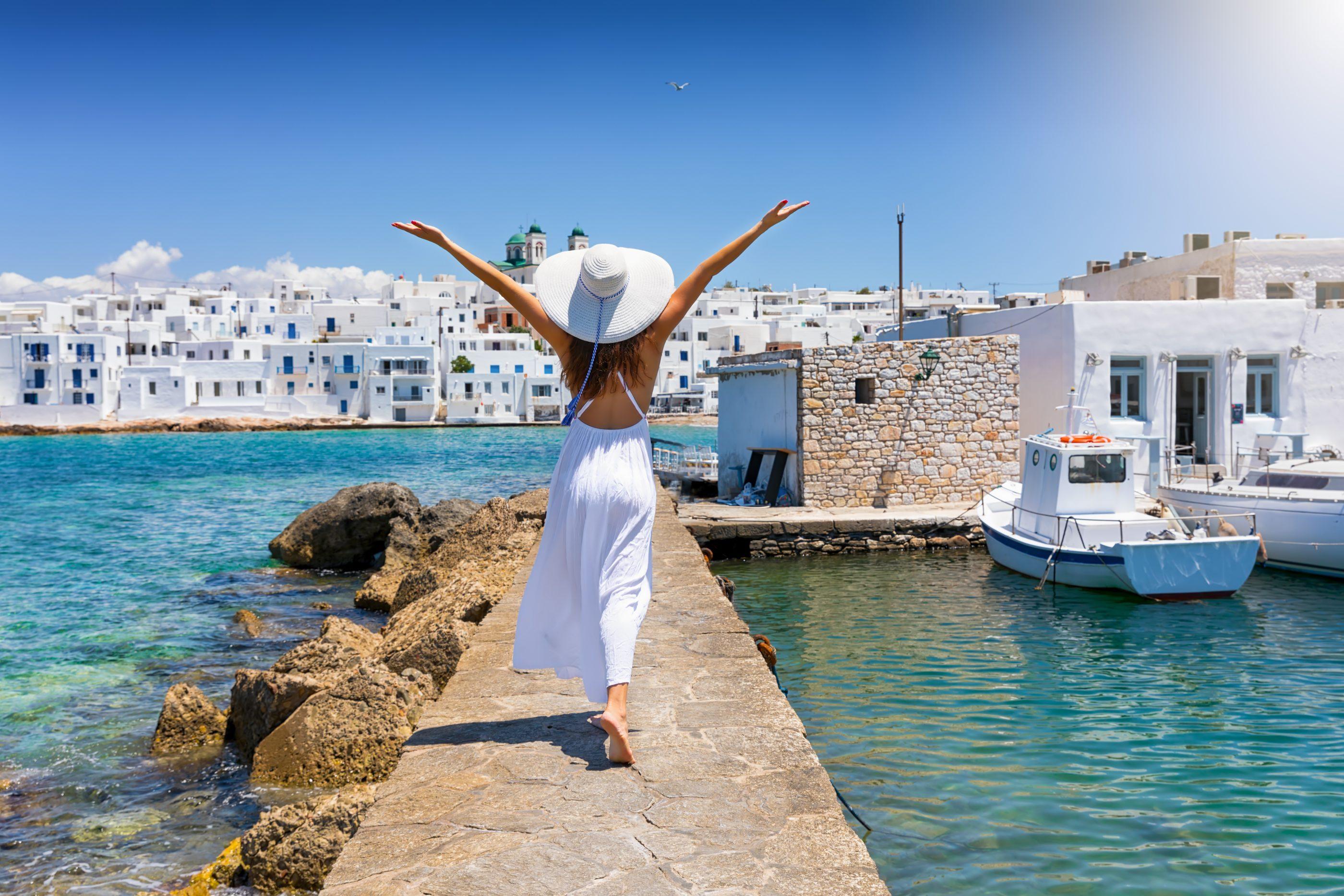 happy lady traveler overlooking greek town and marina off luxury yacht charter vacation