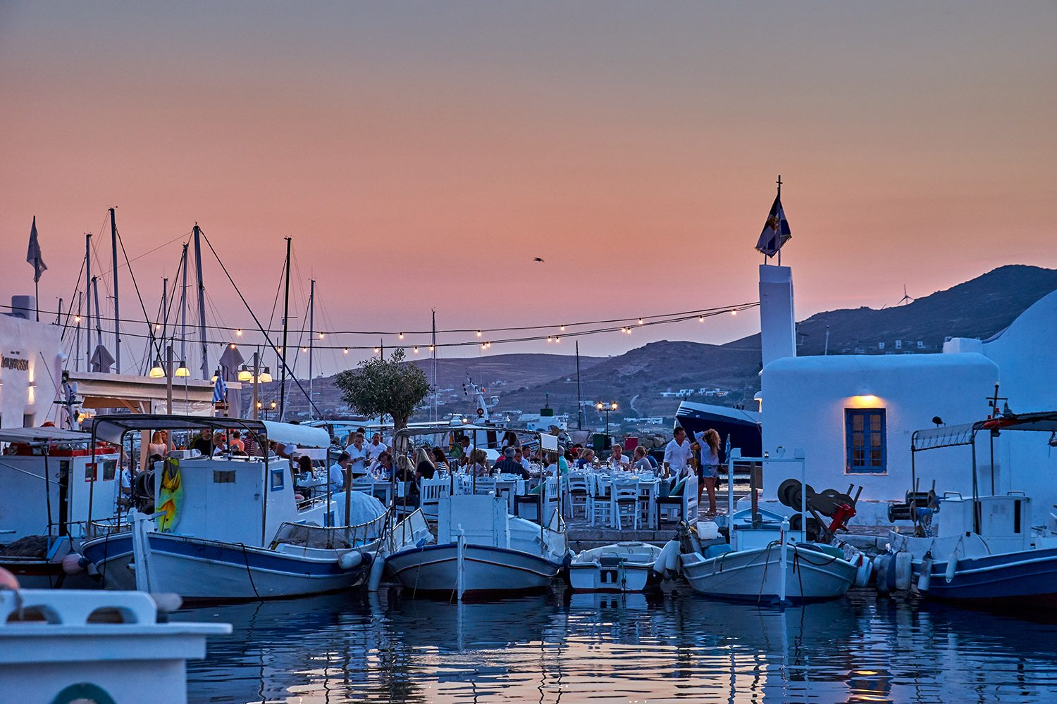 beautiful sunset skyline view from yacht of Paros Island Greece town and marina Scenery