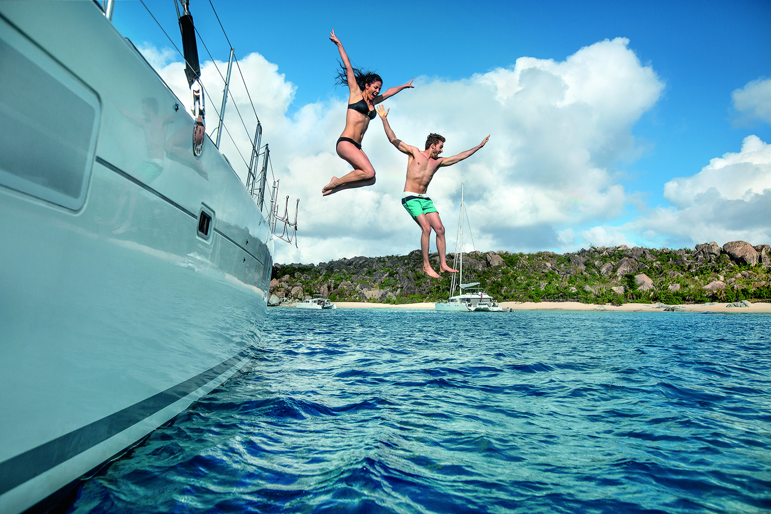 Couple jumping Off boat BVI