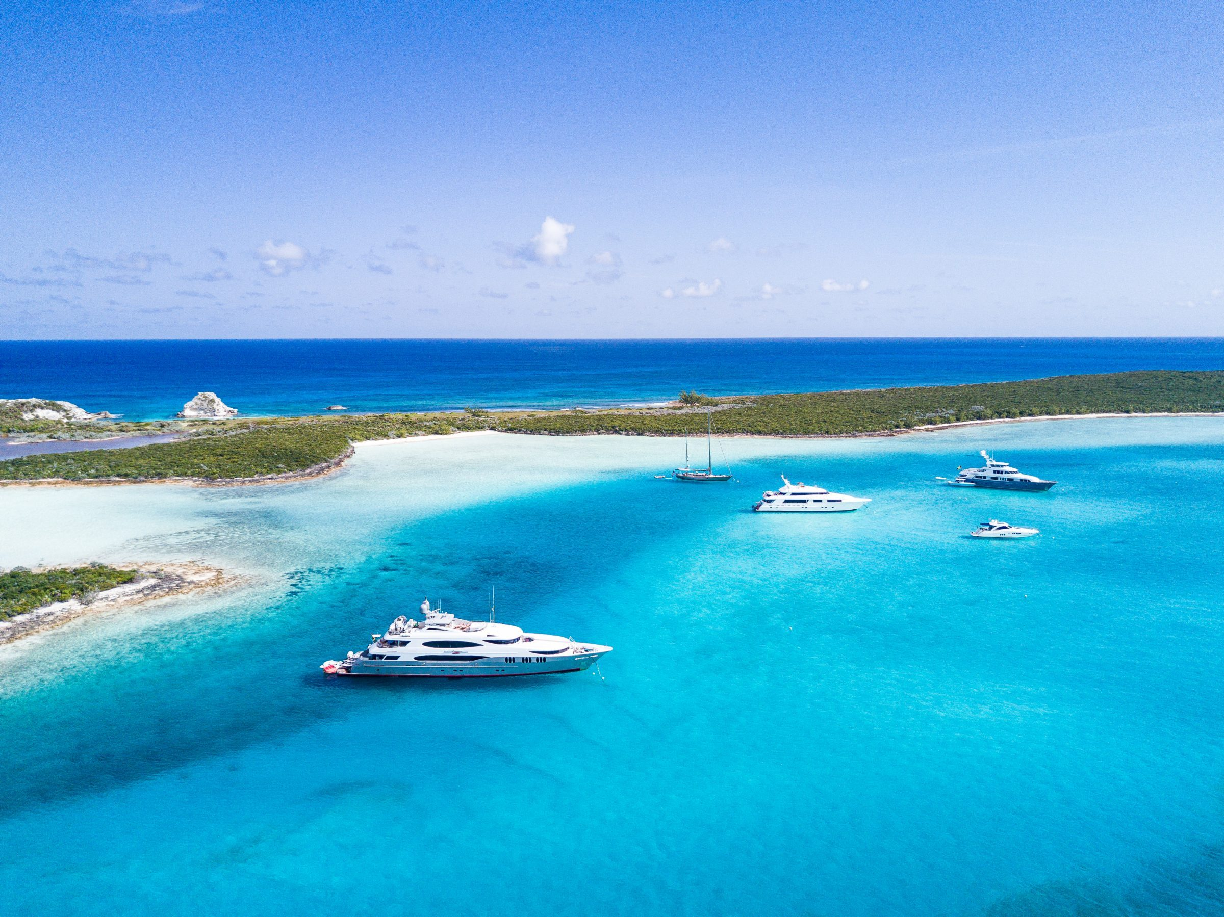 group of tandem superyacht charters at anchor in blue caribbean waters of bahamas