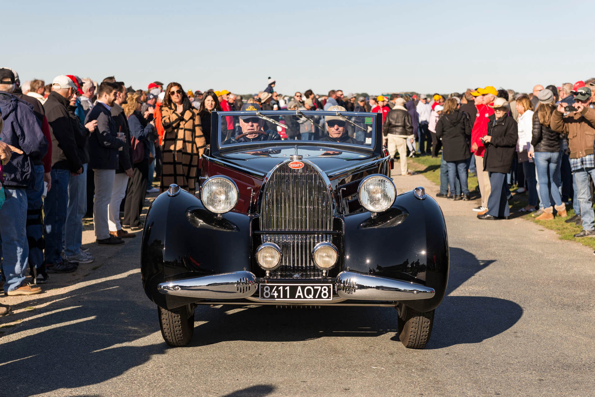 People surrounding a classic Bugati at Audrain's Newport Concours Motor Week