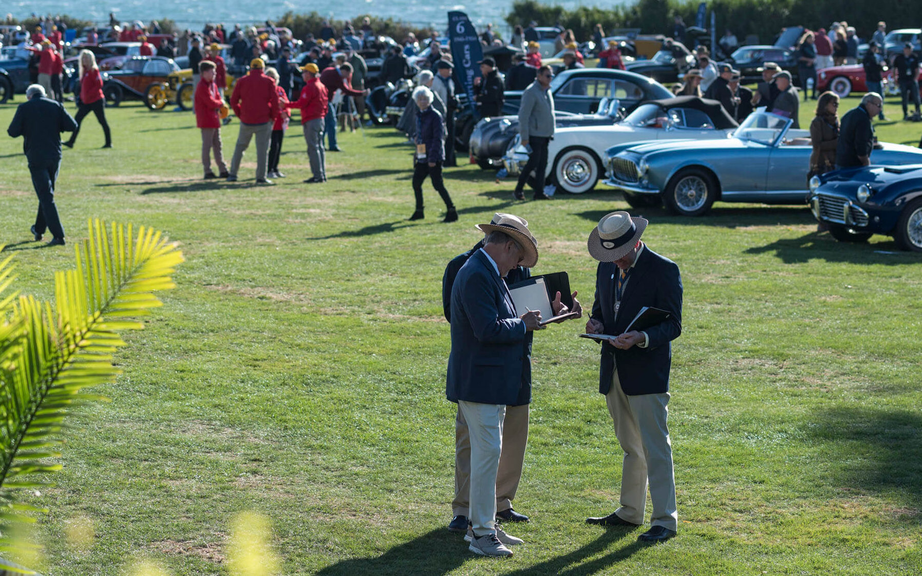 Judges taking notes as they view the cars on display at Audrain's Newport Concours Motor Week