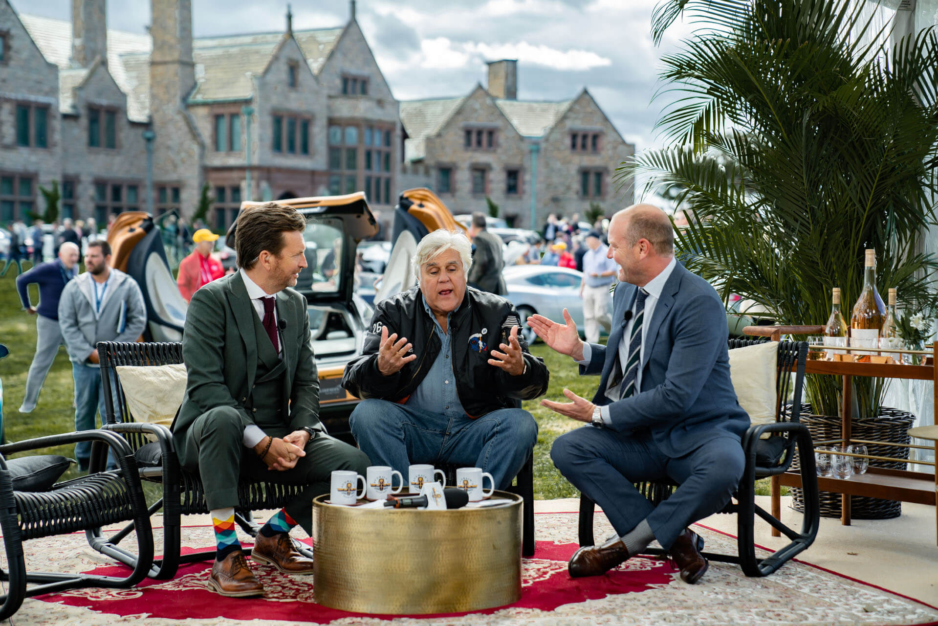 Jay Leno sitting and talking with two men at the Gathering at Audrain's Newport Concours Motor Week