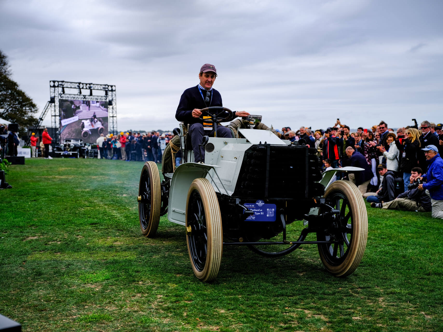 Man driving a classic car in a parade at Audrain's Newport Concours Motor Week