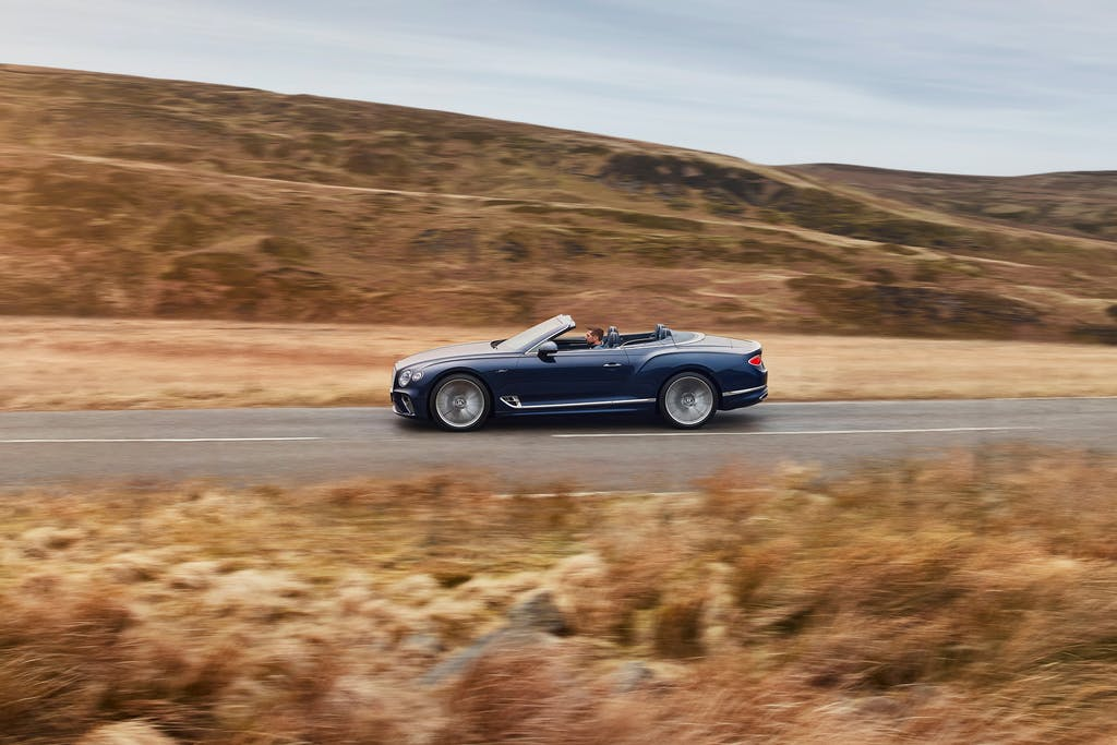 Bentley Continental GT Speed in blue driving along a deserted road