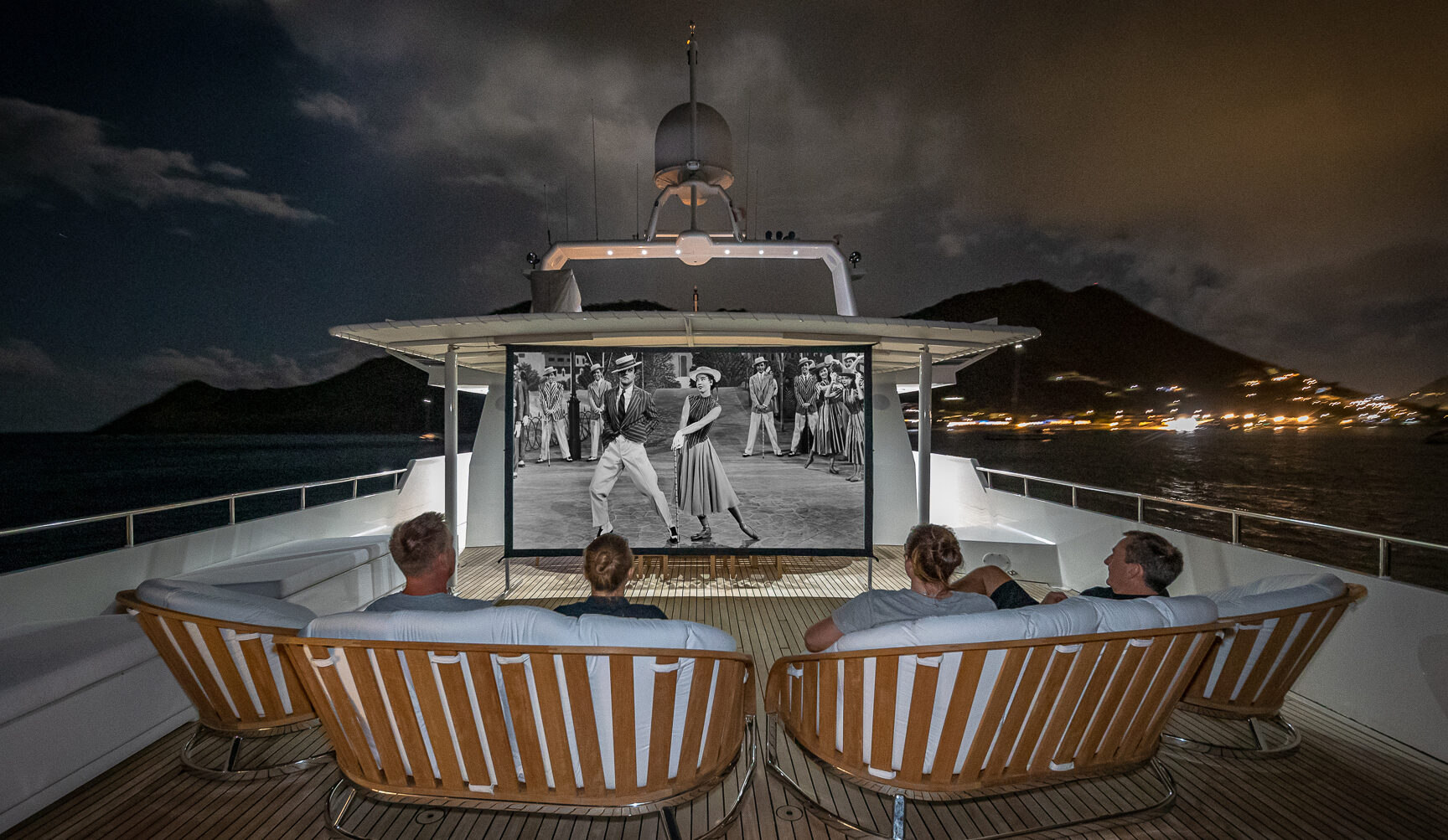 People watching a black and white movie on a projector screen on charter yacht LIONSHARE