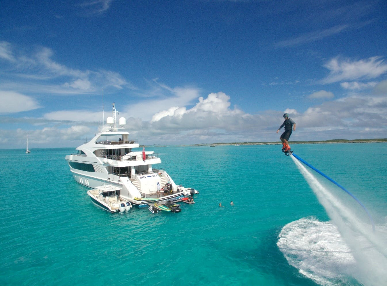 Guest jet packing next to charter yacht BIG SKY on water.