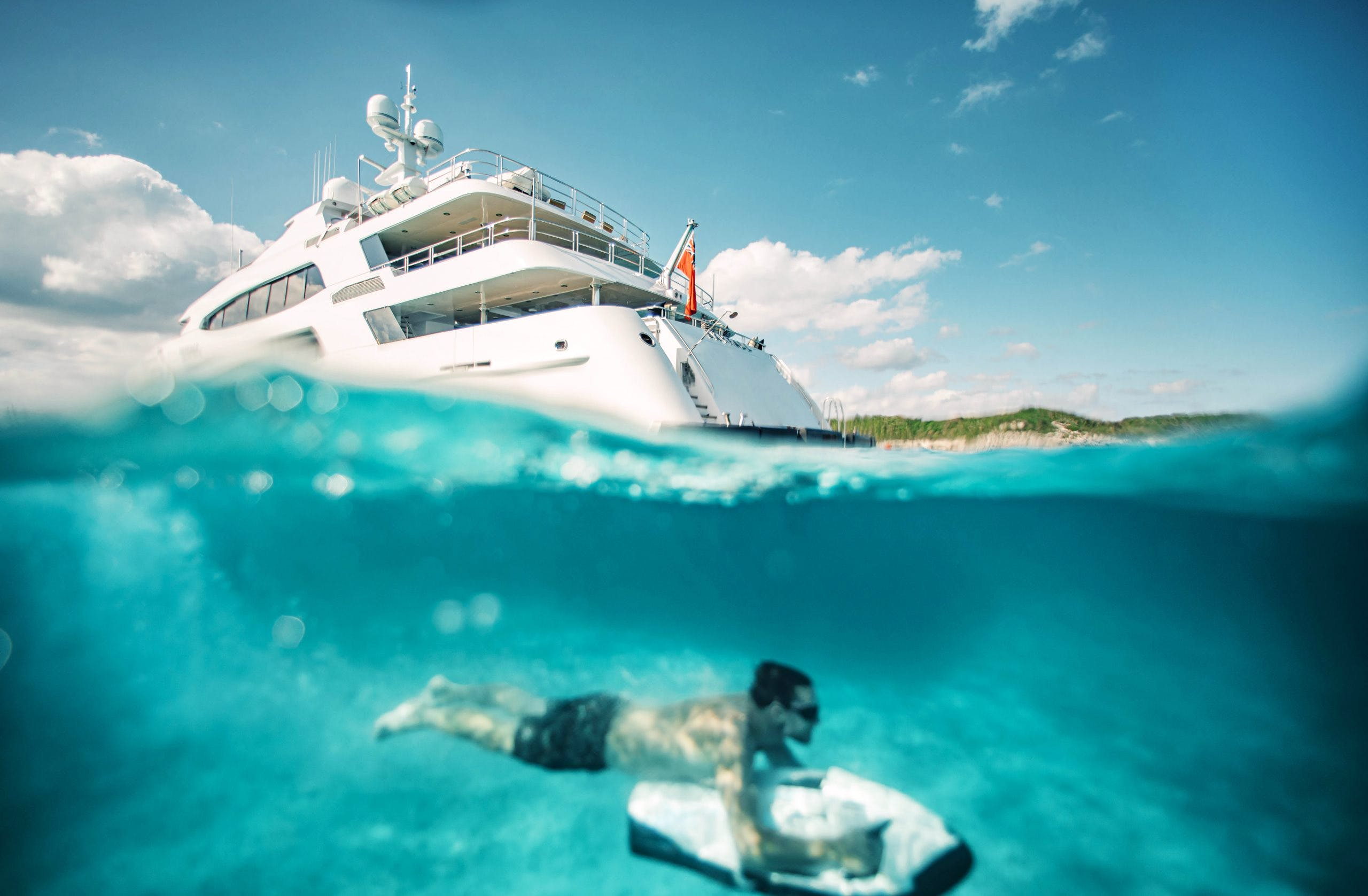 Guest diving under charter yacht SKYFALL with toy.