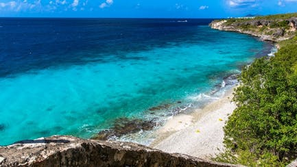 luxury yacht for charter in Bonaire cruising near idyllic island in crystal blue Caribbean Sea
