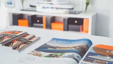Brochures over white desk with model of yacht for sale on the background