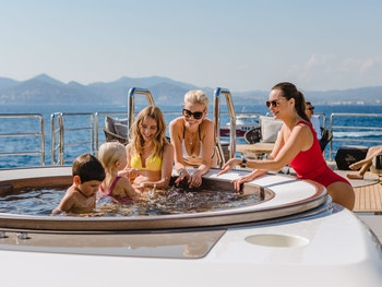 Family in a Jacuzzi on a luxury yacht charter in the mediterranean