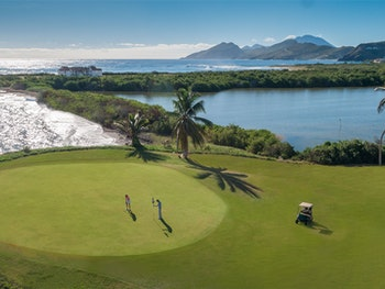 couple golfing in St. Kitts on Caribbean luxury holiday