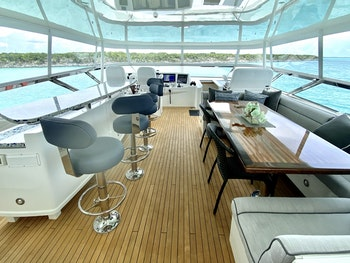 80-foot (24m) Hatteras Charter Yacht CHELSEA flybridge with a bar and multiple social areas